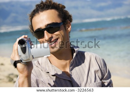Mid-adult Caucasian man on beach pointing video camera at viewer. - stock photo