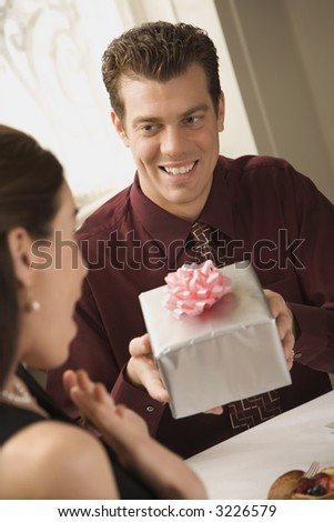 Mid adult Caucasian man presenting wrapped gift to surprised woman at restaurant. - stock photo