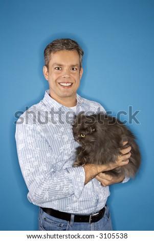 Mid-adult Caucasian man standing holding Persian cat. - stock photo