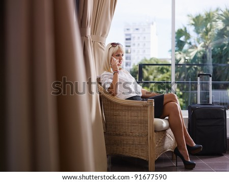 Mid adult caucasian manager speaking on cell phone in hotel room during business trip. Side view, full length, copy space - stock photo