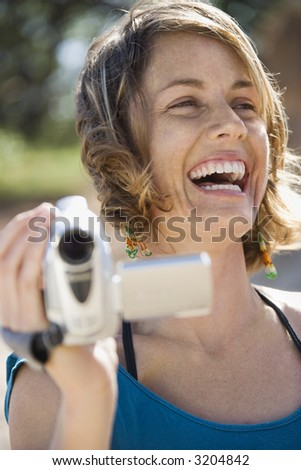Mid-adult Caucasian woman outdoors holding video camera laughing. - stock photo