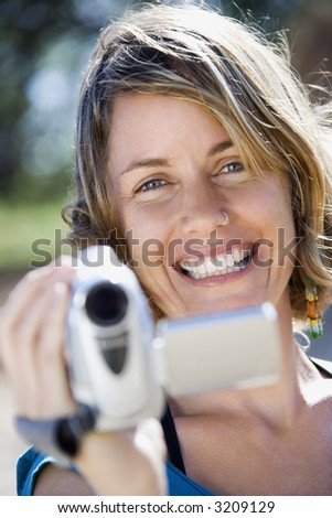 Mid-adult Caucasian woman outdoors pointing video camera at viewer. - stock photo