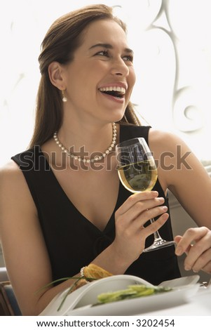 Mid adult Caucasian woman smiling and drinking white wine in restaurant. - stock photo