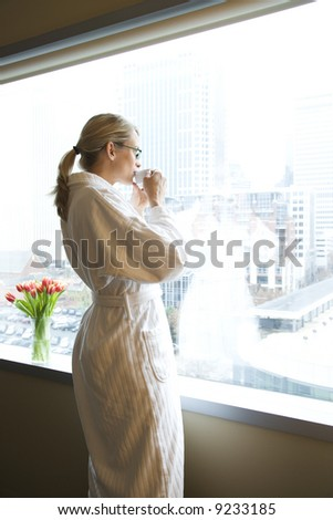 Mid-adult Caucasian woman with coffee cup looking out window. - stock photo