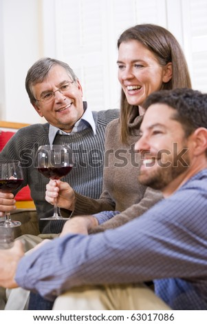 Mid-adult couple and senior parent drinking wine together - stock photo