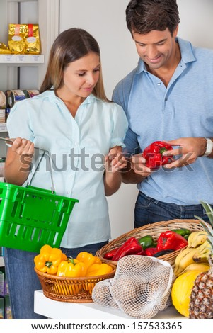 Mid adult couple buying vegetables in grocery store - stock photo