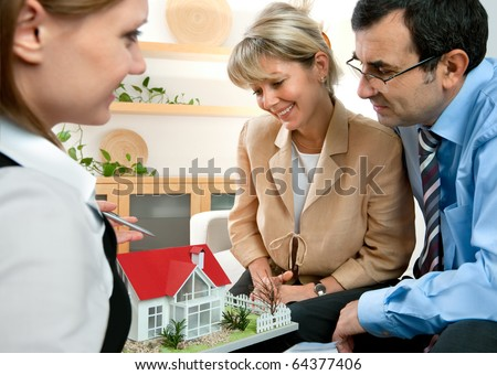 mid-adult couple discussing  with consultant, real estate agent or architect - stock photo