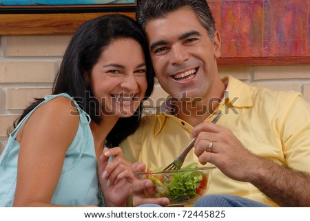 Mid adult couple eating and sharing in a living room.