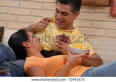 Mid adult couple eating fruits in a living room. - stock photo