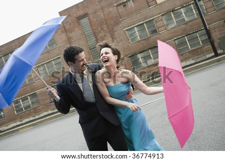 Mid adult couple holding umbrellas in a windy day and laughing - stock photo