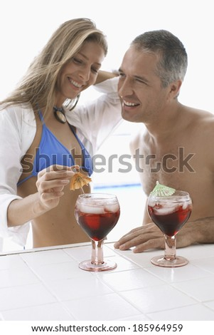 Mid adult couple in beach attire having cocktails - stock photo