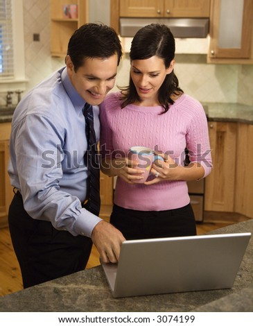 Mid-adult couple looking at laptop computer while standing in kitchen.