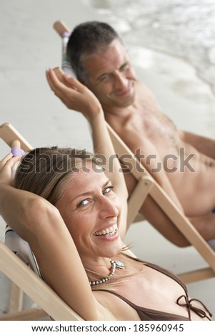 Mid adult couple on lounge chairs on beach - stock photo