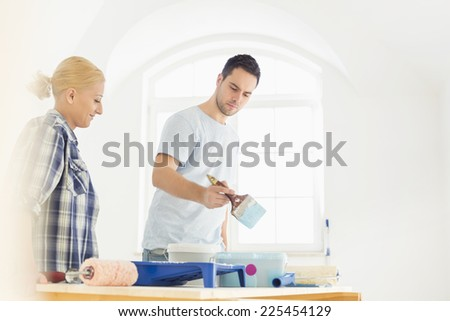Mid-adult couple painting in new house - stock photo