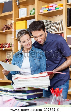 Mid adult couple selecting papers together in store - stock photo
