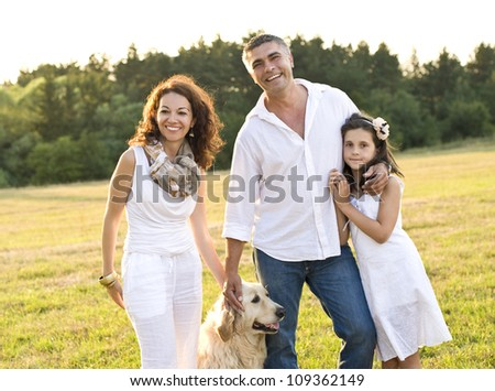 Mid adult couple with daughter and dog in the park - stock photo