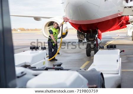 Mid Adult Crew Member Charging Airplane On Runway