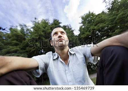 Mid adult (early 30's) caucasian man looking to the distance with an enigmatic confident gaze while indulging in self-photography at the park. - stock photo