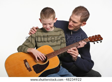 mid-adult father smiling and teaching elementary age son how to play guitar - stock photo