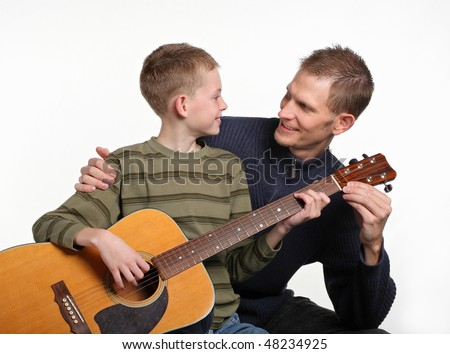 mid-adult father smiling and teaching elemetary age son how to play guitar - stock photo