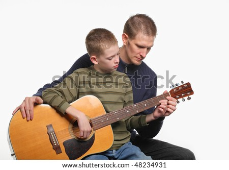 mid-adult father teaching preteen son how to play acoustic guitar - stock photo