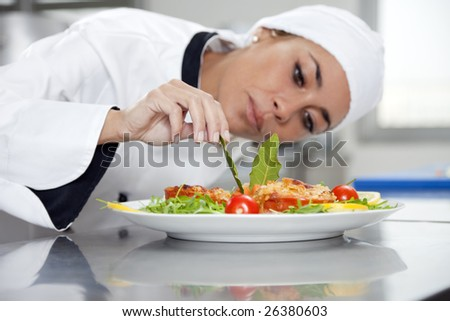 mid adult female chef in kitchen decorating dish - stock photo