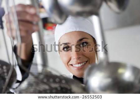 mid adult female chef taking kitchen utensil - stock photo