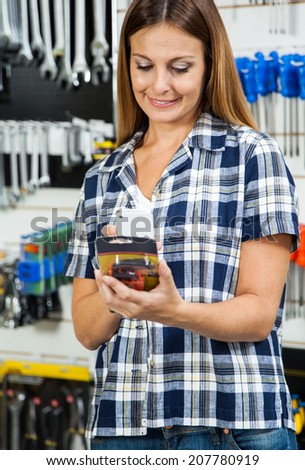 Mid adult female customer scanning product's barcode on mobilephone in hardware store - stock photo