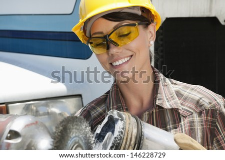 Mid adult female industrial worker buffing a truck engine cylinder - stock photo