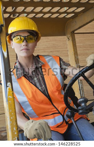 Mid adult female industrial worker driving forklift truck - stock photo
