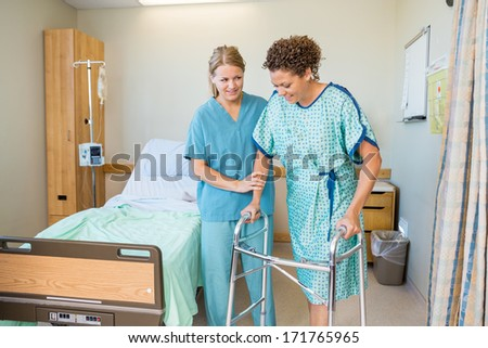Mid adult female nurse helping patient to walk using walker in hospital - stock photo