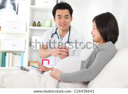 Mid adult female patient for medical check up at clinic with doctor on background