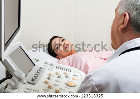 Mid adult female patient for ultrasound check up at clinic with doctor in foreground - stock photo
