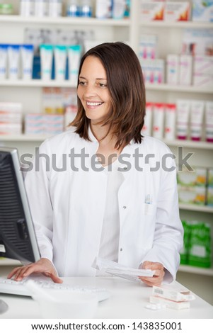Mid adult female pharmacist using computer while holding prescription paper at desk