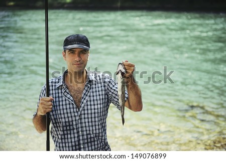 mid adult fisherman on holidays on river, relaxing and fishing trout. Copy space - stock photo