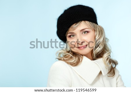 mid adult happy attractive woman gives a wink, winter portrait of attractive caucasian middle aged 40 years old lady in coat and hat over blue