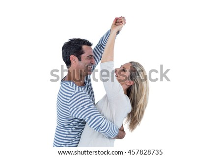 Mid adult happy couple dancing against white background