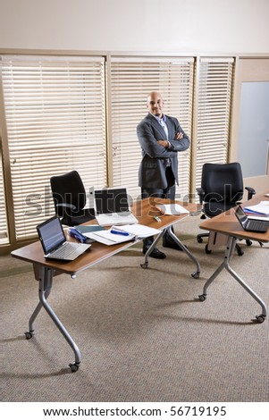 Mid-adult Hispanic businessman standing alone in office