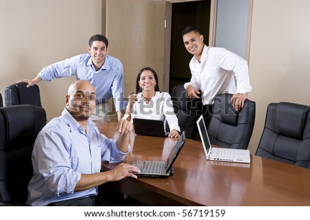 Mid-adult Hispanic office workers in boardroom meeting with laptops - stock photo