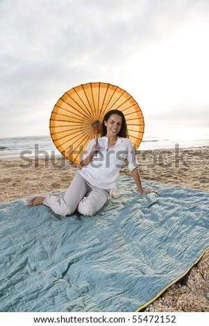 Mid-adult Hispanic woman with parasol on beach blanket - stock photo