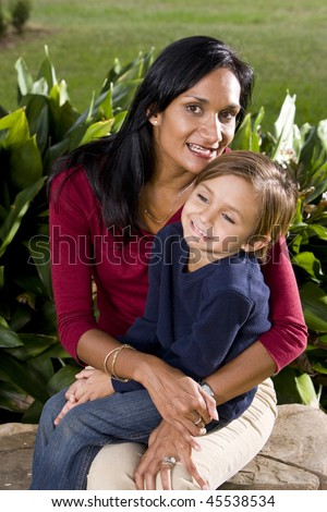 Mid-adult Indian mother holding 5 year old son on lap in park - stock photo