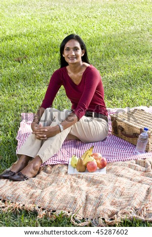 Mid-adult Indian woman sitting on picnic blanket on grass in park - stock photo