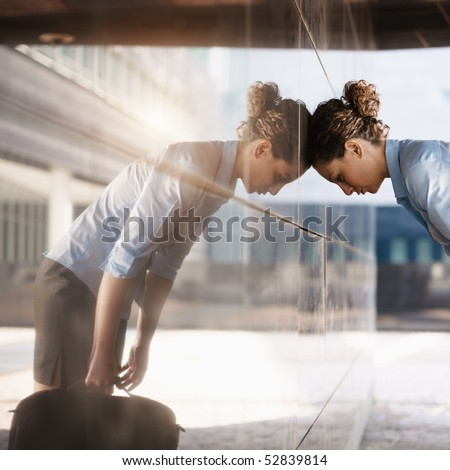 mid adult italian business woman banging her head against a wall outside office building. Square shape, copy space - stock photo