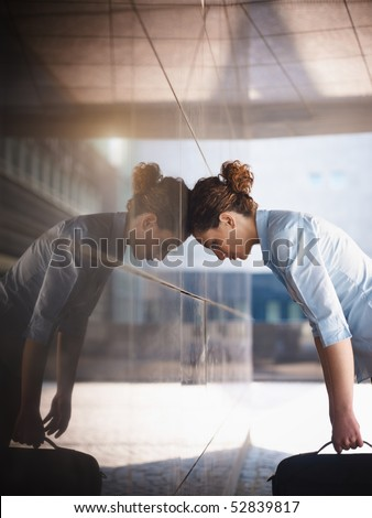 mid adult italian business woman banging her head against a wall outside office building. Vertical shape, copy space