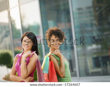 mid adult italian woman and hispanic woman carrying shopping bags out of shopping center. Horizontal shape, waist up, copy space - stock photo