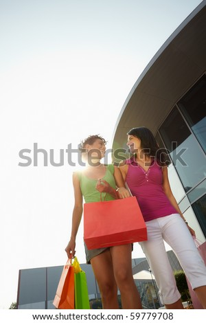 mid adult italian woman and hispanic woman carrying shopping bags out of shopping center at sunset. Vertical shape, low angle view, copy space - stock photo