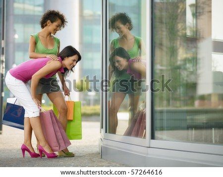 mid adult italian woman and hispanic woman looking at shop window with shopping bags. Horizontal shape, full length, copy space - stock photo