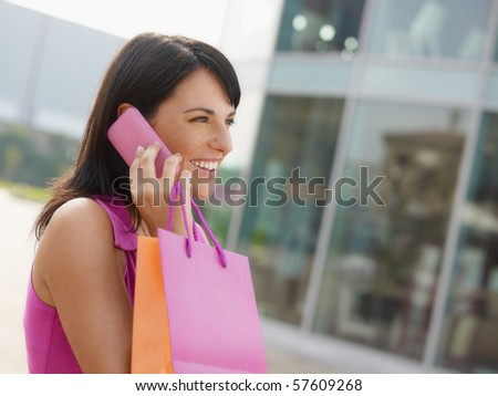 mid adult italian woman talking on mobile phone out of shopping center. Horizontal shape, head and shoulders, copy space - stock photo