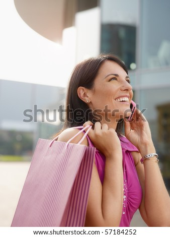 mid adult italian woman talking on mobile phone out of shopping center. Vertical shape, head and shoulders, copy space - stock photo