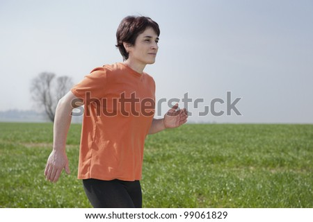 Mid adult jogging woman - stock photo